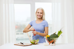 Smiling woman cooking vegetable salad at home Stock Photo