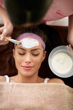 Smiling woman on cosmetic treatment of her face skin Royalty Free Stock Photos