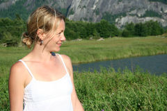 Smiling woman in countryside. Side portrait of smiling blond haired young woman in countryside with lake or river in background Stock Photography