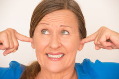 Smiling woman covering ears Stock Photography