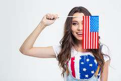 Smiling woman covering her eye with USA flag. Portrait of a smiling woman covering her eye with USA flag isolated on a white background Royalty Free Stock Photo