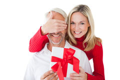 Smiling woman covering partners eyes and holding gift Stock Photography