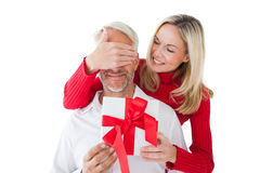 Smiling woman covering partners eyes and holding gift Royalty Free Stock Images