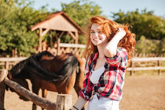 Smiling woman cowgirl with horse sitting on ranch. Smiling pretty young woman cowgirl with horse sitting on ranch Royalty Free Stock Photos