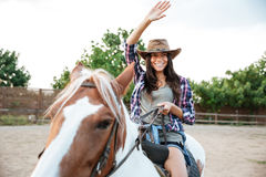 Smiling woman cowgirl riding a horse outdoors Royalty Free Stock Photo