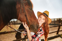 Smiling woman cowgirl standing with her horse on farm Royalty Free Stock Photography