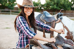 Smiling woman cowgirl standing and preparing saddle for riding horse. Smiling pretty young woman cowgirl standing and preparing saddle for riding horse Royalty Free Stock Photos