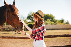 Smiling woman cowgirl taking care of her horse on farm. Smiling redhead young woman cowgirl taking care of her horse on farm royalty free stock photos
