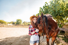 Smiling woman cowgirl walking with her horse in village Stock Images