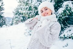 Smiling woman in cozy knitting pullover and fur hat stay om wint. Er forest glade Stock Images