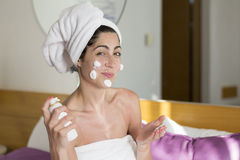 Smiling  woman with cream on her face Royalty Free Stock Photography