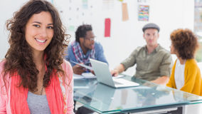 Smiling woman with creative team working behind Stock Photos