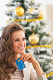 Smiling woman with credit card in front of christmas  tree Royalty Free Stock Image