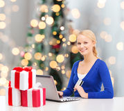 Smiling woman with credit card and laptop Stock Photo