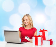 Smiling woman with credit card and laptop. Christmas, holidays, technology and shopping concept - smiling woman in red blank shirt with gift boxes, credit card Stock Photos