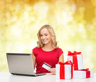 Smiling woman with credit card and laptop. Christmas, holidays, technology and shopping concept - smiling woman in red blank shirt with gift boxes, credit card Royalty Free Stock Images