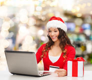 Smiling woman with credit card and laptop Royalty Free Stock Photos