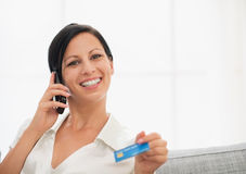 Smiling woman with credit card speaking mobile Royalty Free Stock Photos