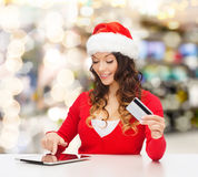 Smiling woman with credit card and tablet pc Stock Images