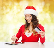 Smiling woman with credit card and tablet pc Stock Photos
