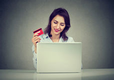 Smiling woman with credit card using laptop shopping online Royalty Free Stock Photos