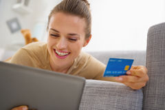 Smiling woman with credit card using tablet pc while laying on sofa Stock Photo