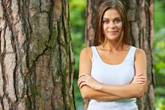 Smiling woman with crossed arms standing in forest. Royalty Free Stock Photos