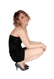Smiling woman crouching on floor. A beautiful young Caucasian woman crouching on the Royalty Free Stock Photography