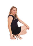 Smiling woman crouching on floor. A lovely blond woman in a black dress and high heels crouching on the Royalty Free Stock Photos