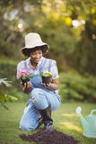 Smiling woman crouching in the garden Royalty Free Stock Images