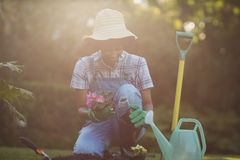 Smiling woman crouching in the garden Stock Images
