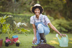 Smiling woman crouching in the garden. Looking at the camera Stock Photos