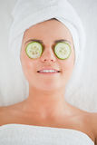 Smiling woman with cucumber slices on the face Stock Photo