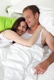 Smiling woman cuddling her husband in bed Royalty Free Stock Image