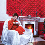 Smiling woman with a cup of coffe in a red vintage room with chr Royalty Free Stock Image