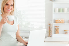 Smiling woman with a cup of coffee and a laptop. Looking into the camera in the kitchen Stock Photos