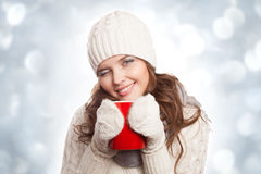 Smiling woman with a cup of coffee on the winter background. Royalty Free Stock Image