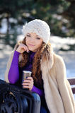 Smiling woman with cup of coffee in the winter park.  Stock Photos