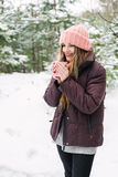 Smiling woman with cup of hot tea in woolen hat Stock Images