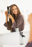 Smiling woman curling hair with straightener Royalty Free Stock Photography