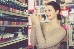 Smiling woman customer browsing rows of lipstick Royalty Free Stock Images