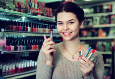 Smiling woman customer browsing rows of lipstick Stock Photo
