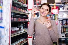 Smiling woman customer browsing rows of lipstick Royalty Free Stock Photos