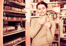 Smiling woman customer browsing rows of lipstick Royalty Free Stock Photography