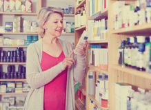 Smiling woman customer browsing rows of skin care products Stock Photo