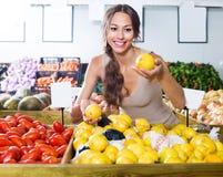 Smiling woman customer choosing lemons royalty free stock image