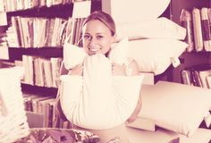 Smiling woman customer holding downy pillow Stock Photo