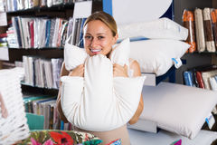 Smiling woman customer holding downy pillow Stock Images
