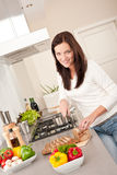 Smiling woman cutting bread in the kitchen. Looking at camera Royalty Free Stock Image