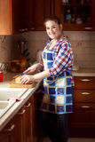 Smiling woman cutting bread on wooden cutting board Stock Image